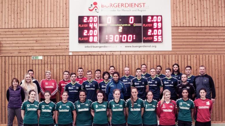 Die Spielerinnen und Spieler der TuS 05 Daun Handballabteilung vor der durch den Bürgerdienst gesponserten Anzeigetagel in der Dauner Wehrbüschturnhalle