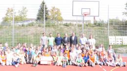 Foto auf dem neuen Spielfeld: Schülerinnen und Schüler der Klassen 5a - 5c; stehend von rechts: Fr. Stölben (Förderverein GSG), H. Brill (Vermessungsbüro D. Brill), Kreissparkasse (H. Hennen und H. Pitzen), H. Winbush (BÜRGERDIENST e.V.), T. Feilen und F. Henschel (Sportlehrer am GSG)