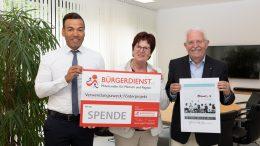 """Tyrone Winbush (Mitglied des Vorstands des BÜRGERDIENST e.V.) übergibt den Initiatoren Margot Bangert und SR Dr. Volkhard Bangert den symbolischen Spendenscheck zur Unterstützung des """"Mus-e""""-Projekts."""