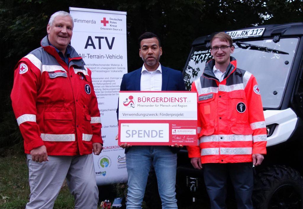 Tyrone Winbush (Vorstandsmitglied des BÜRGERDIENST e.V.) bei der Spendenübergabe mit Dr. Rafael Hoffmann (links, Vorsitzender des DRK Ortsverein Daun) und Christoph Schäfer (rechts, Besitzer des DRK Ortsverein Daun).