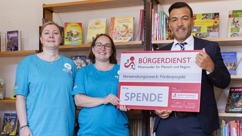 V.l.n.r.: Sandra Gitzen (Stv. Leitung Bücherei Darscheid), Katharina Holz (Leitung Bücherei Darscheid) mit Tyrone Winbush (BÜRGERDIENST e. V.)